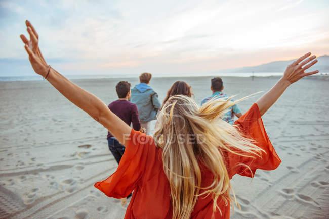 Gruppe von Freunden zu Fuß am Strand, junge Frau mit den Armen in der Luft, Rückansicht — Stockfoto