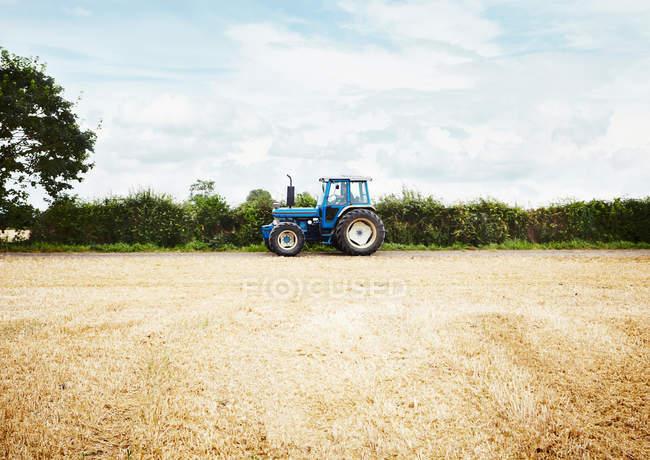 Conduite d'un tracteur dans un champ de culture labouré — Photo de stock
