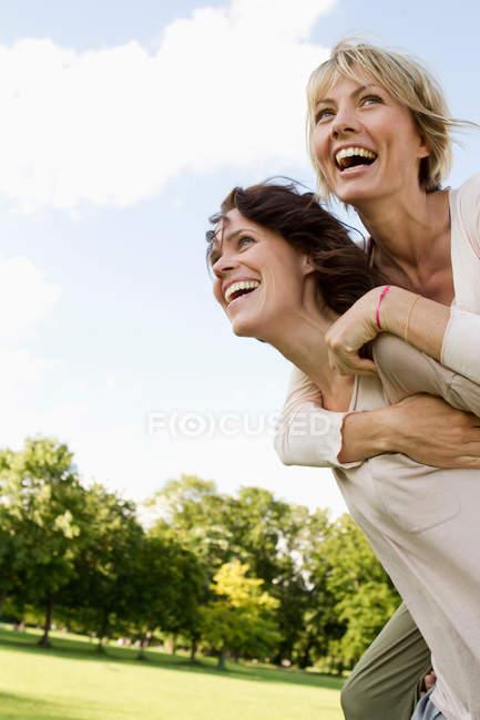 Donna dando il suo amico un piggy indietro — Foto stock