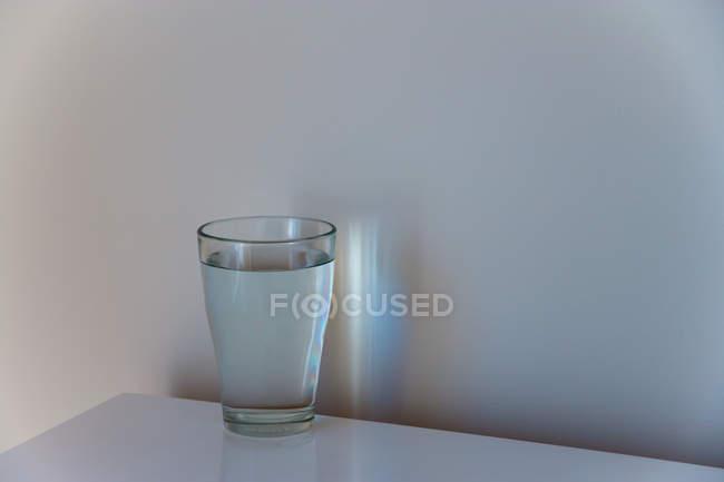 Натюрморт стакан воды на столе — стоковое фото
