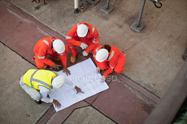Workers with blueprints at oil refinery — Stock Photo