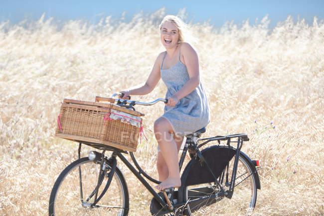 Жінка їзда на велосипеді у високій траві — стокове фото