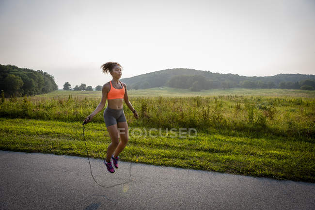 Young woman training with skipping rope in rural park — Stock Photo