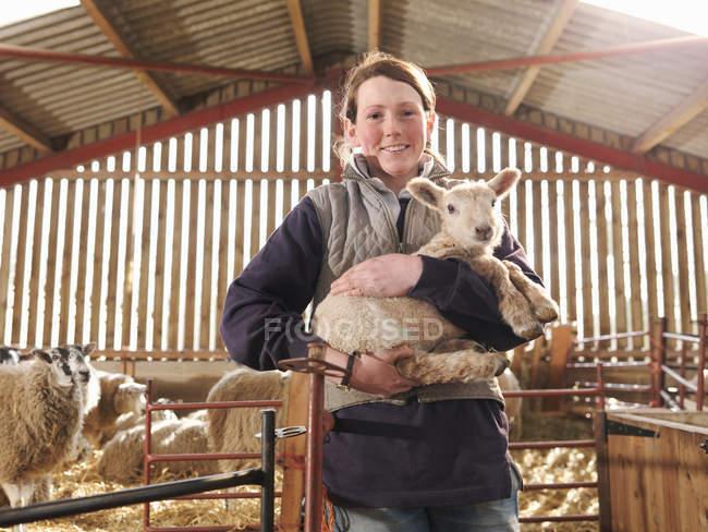 Fazendeiro fêmea segurando cordeiro — Fotografia de Stock