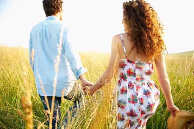 Пара держащихся за руки на пшеничном поле — стоковое фото