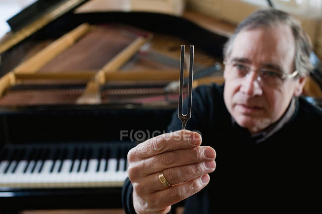 Piano tuner holding tuning fork — Stock Photo