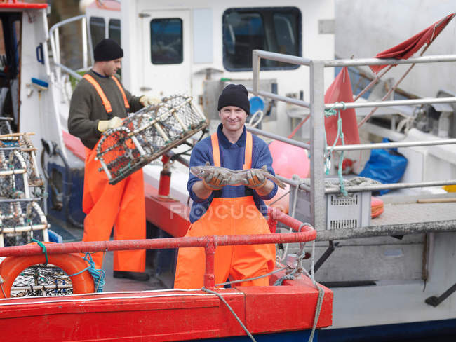 Fisherman holding fish on boat in harbour — Stock Photo