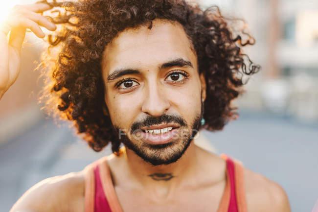Retrato de la ciudad de un joven con la mano en el pelo rizado - foto de stock