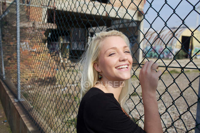 Mulher sorridente encostada à cerca — Fotografia de Stock