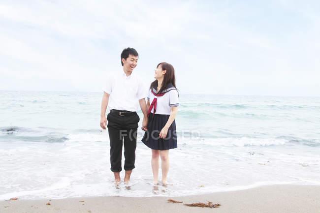 Young couple wearing school uniform standing on sandy beach — Stock Photo