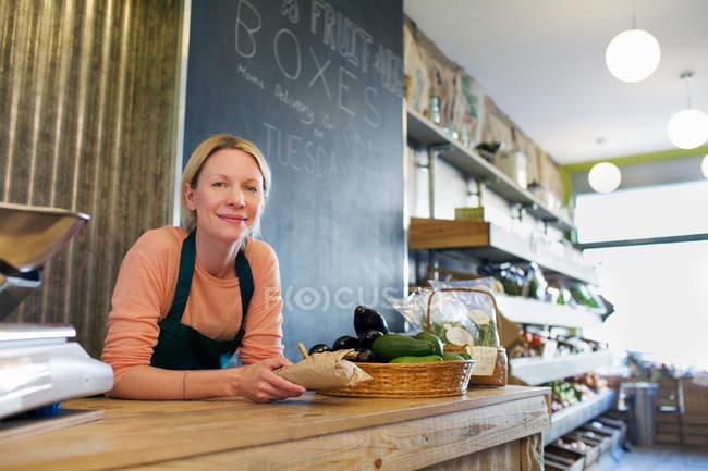 Бакалейщик работает за прилавком в магазине — стоковое фото