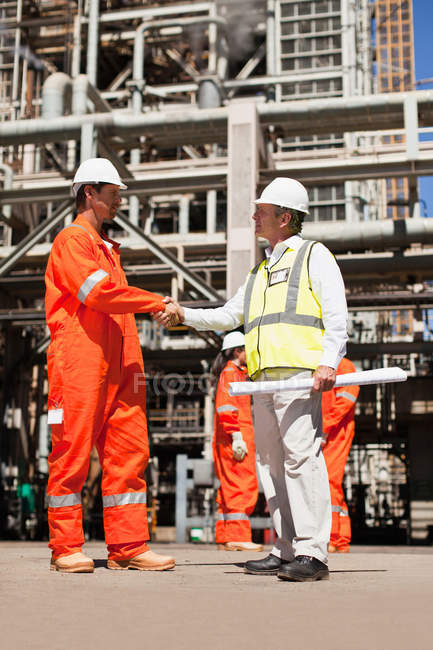 Workers shaking hands at oil refinery — Stock Photo
