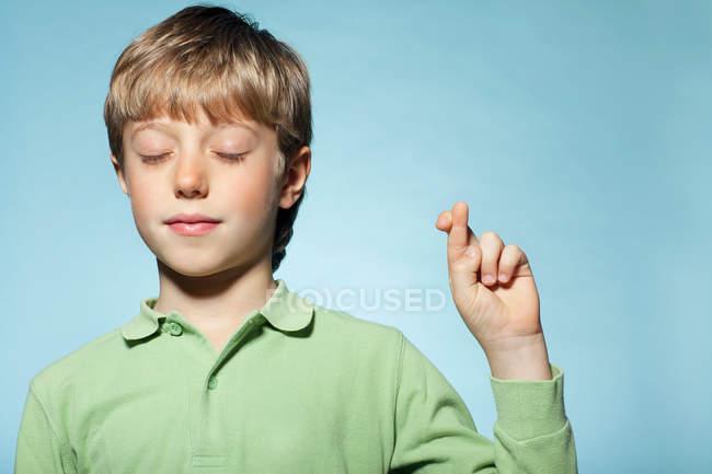 Garçon avec les doigts croisés — Photo de stock