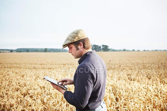 Фермер с помощью планшетного компьютера в поле — стоковое фото