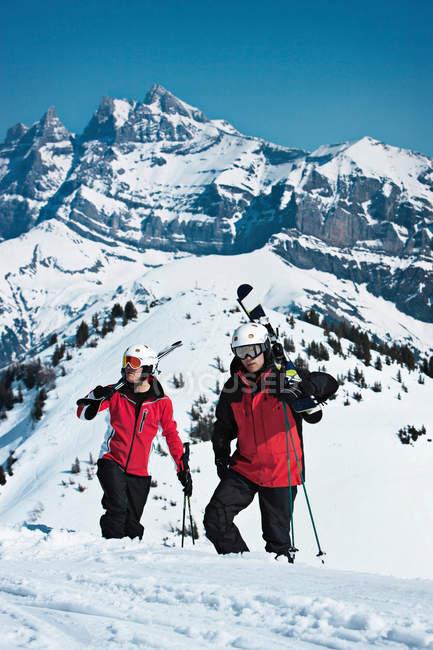 Skiers climbing snowy mountainside — стоковое фото