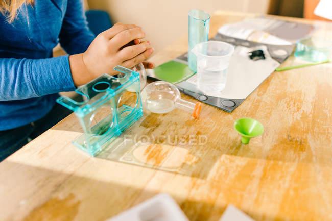 Изображение девушки, готовящейся к научному эксперименту за столом — стоковое фото