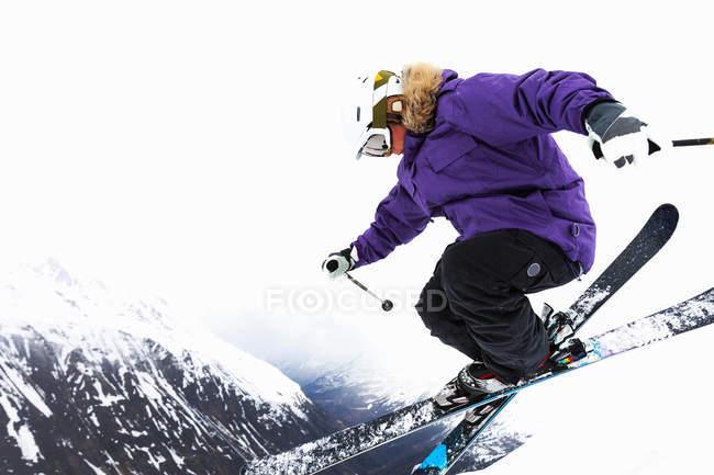 Низкий угол обзора прыжков лыжника на снежном склоне — стоковое фото