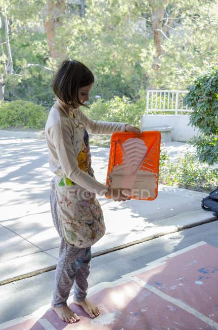 Chica en garaje preparando pintura en bandeja de pintura - foto de stock