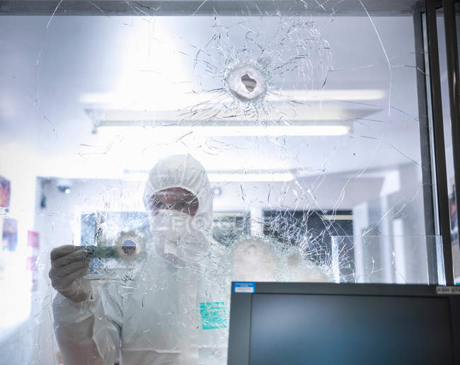Forensic scientist measuring bullet hole in broken glass at crime scene — Stock Photo