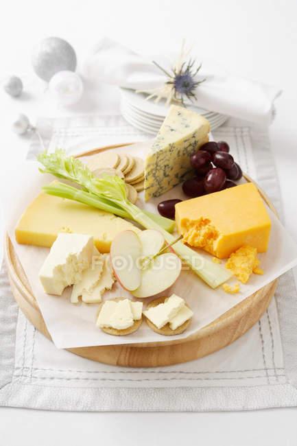 Сыр и фрукты на деревянной доске — стоковое фото
