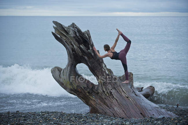 Mature woman practicing yoga position on large driftwood tree trunk at beach — Stock Photo