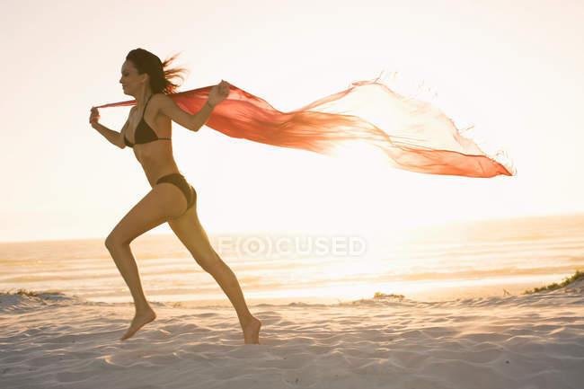 Femme courant avec sarong sur la plage — Photo de stock