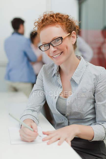 Ділова жінка робить нотатки в нараді — стокове фото