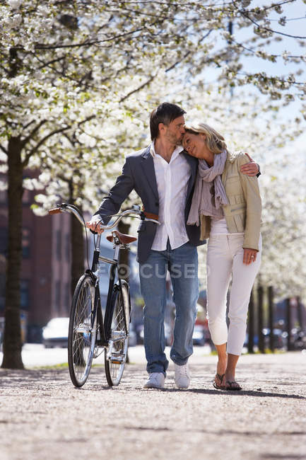Couple walking bicycle in park — Stock Photo