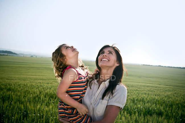 Жінка холдингу дочка і дивлячись на небо — стокове фото