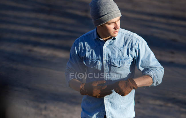 Man pulling off gloves outdoors — Stock Photo