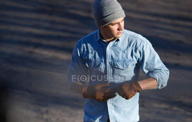 Людина тягнуча off рукавички на відкритому повітрі — стокове фото