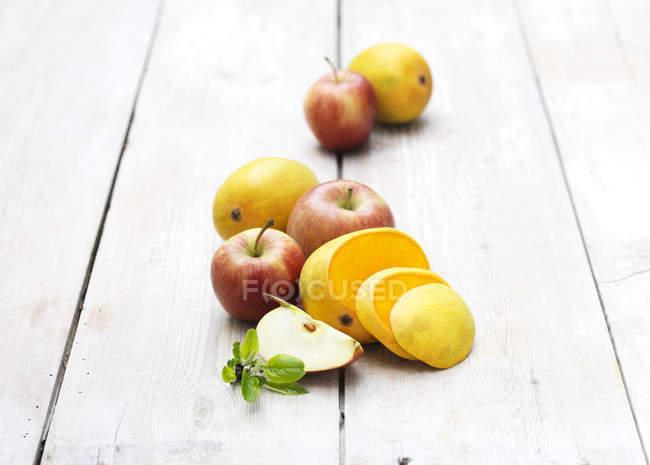 Яблоко и манго ломтиками на белоснежном деревянный стол — стоковое фото