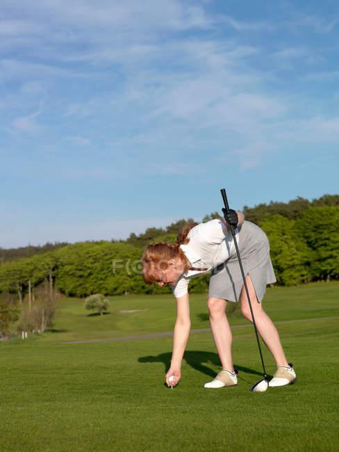 Frau setzt Golf-Abschlag auf Gras — Stockfoto