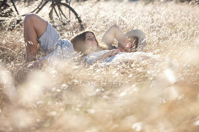Couple laying in tall grass — Stock Photo