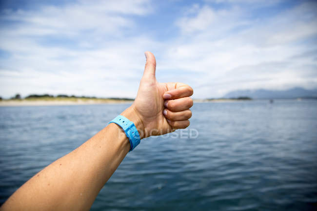 Female hand giving thumbs up over Nehalem Bay, Oregon, USA — Stock Photo