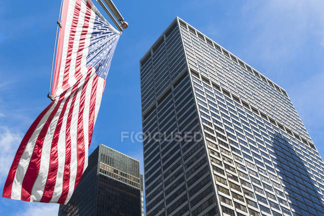 Low angle view of skyscrapers and us flag, Manhattan, New York, USA — Stock Photo