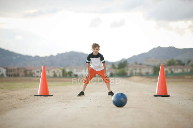 Boy in goal playing football outdoors — Stock Photo