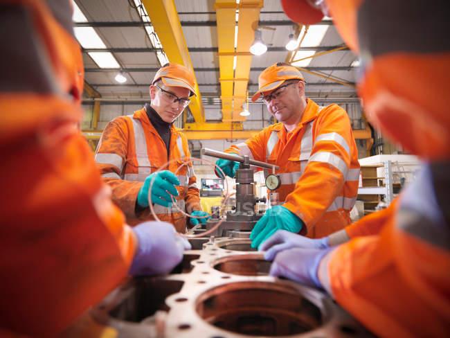 Ingénieur d'apprenti travaillant sur le bloc moteur — Photo de stock