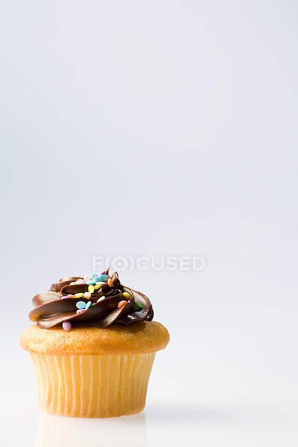 Cupcake decorado con crema de chocolate y sprinkles - foto de stock