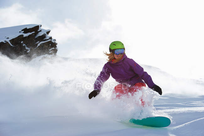 Woman snowboarding down th hill — Stock Photo
