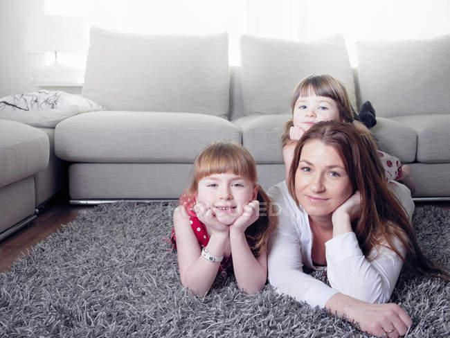 Мать и дочери лежали на ковре — стоковое фото