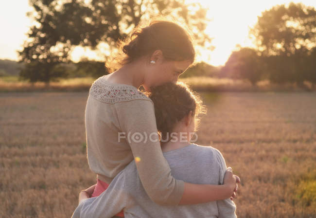 Mother and daughter hugging in field — Stock Photo