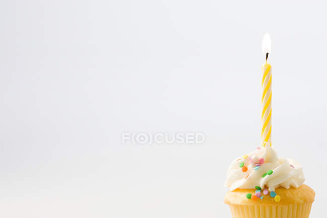 Birthday candle on cupcake decorated with cream and sprinkles — Stock Photo