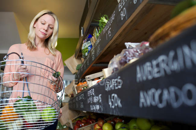 Woman buying produce in store — Stock Photo