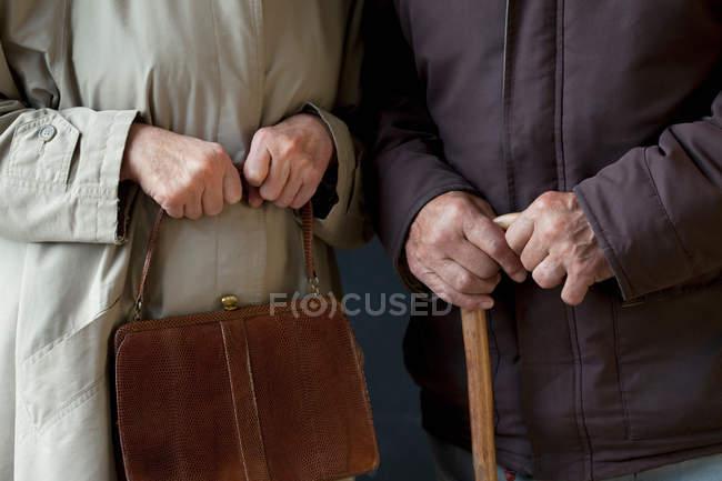 Senior man with walking stick, senior woman with handbag — Stock Photo