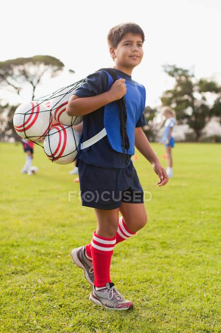 Junge trägt Fußballbälle auf dem Spielfeld — Stockfoto