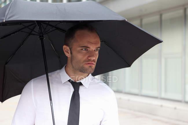 Portrait d'un homme d'affaires marchant sous un parapluie — Photo de stock