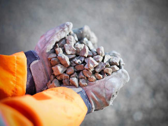 Mains gantées tenant des pierres concassées dans un site de carrière — Photo de stock