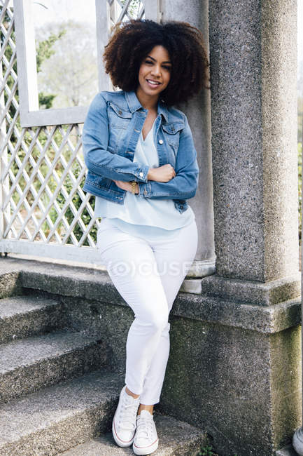Full length front view of mid adult woman, arms crossed, leaning against structure, smiling — Stock Photo