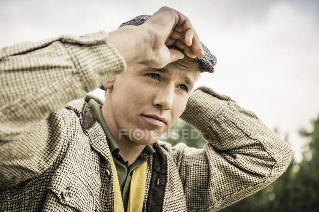 Low angle portrait of young man putting on flat cap looking away — Stock Photo